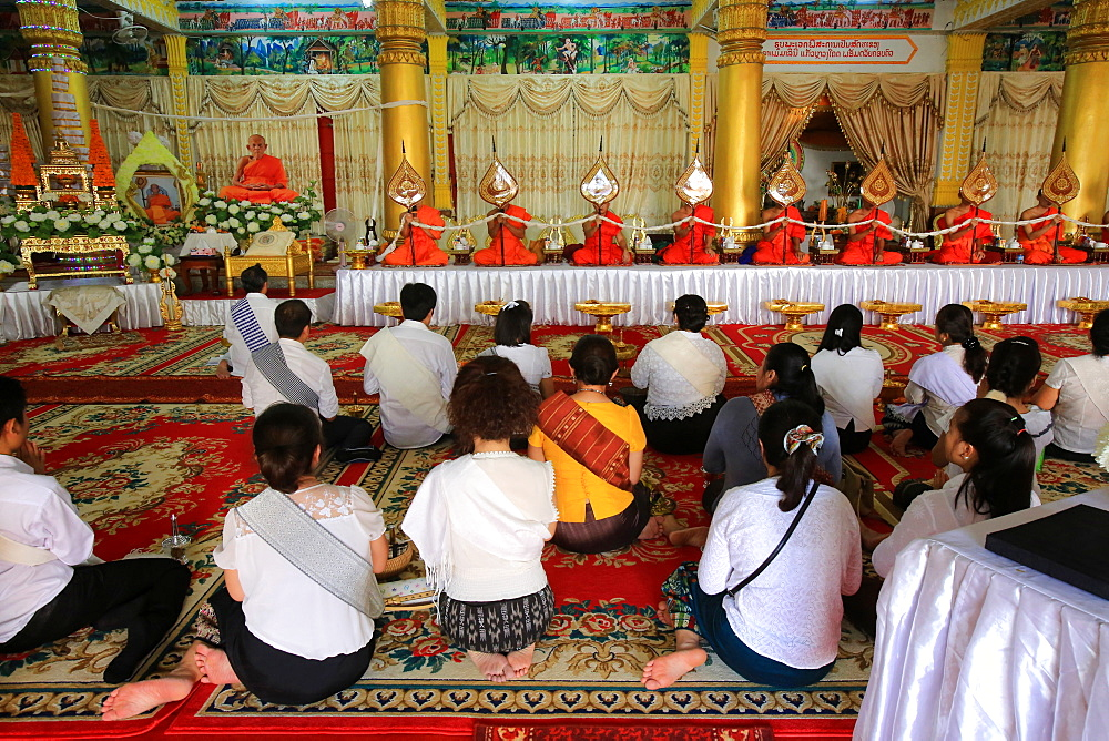 Seated Buddhist monks praying at Remembrance of the deceased. Wat Ong Teu Mahawihan. Temple of the Heavy Buddha. Vientiane. Laos