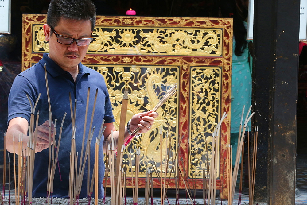 A Chinese man praying and offering incense, Thian Hock Keng Temple, Singapore, Southeast Asia, Asia