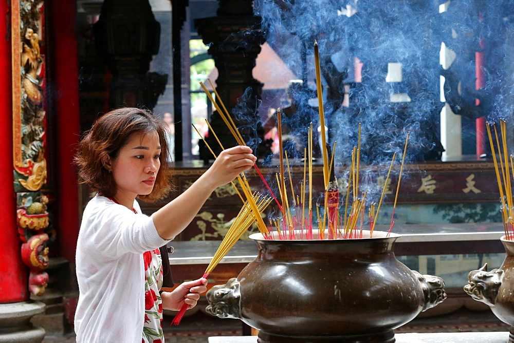 Buddhist worshipper placing incense sticks on joss stick pot, Taoist temple, Phuoc An Hoi Quan Pagoda, Ho Chi Minh City, Vietnam, Indochina, Southeast Asia, Asia