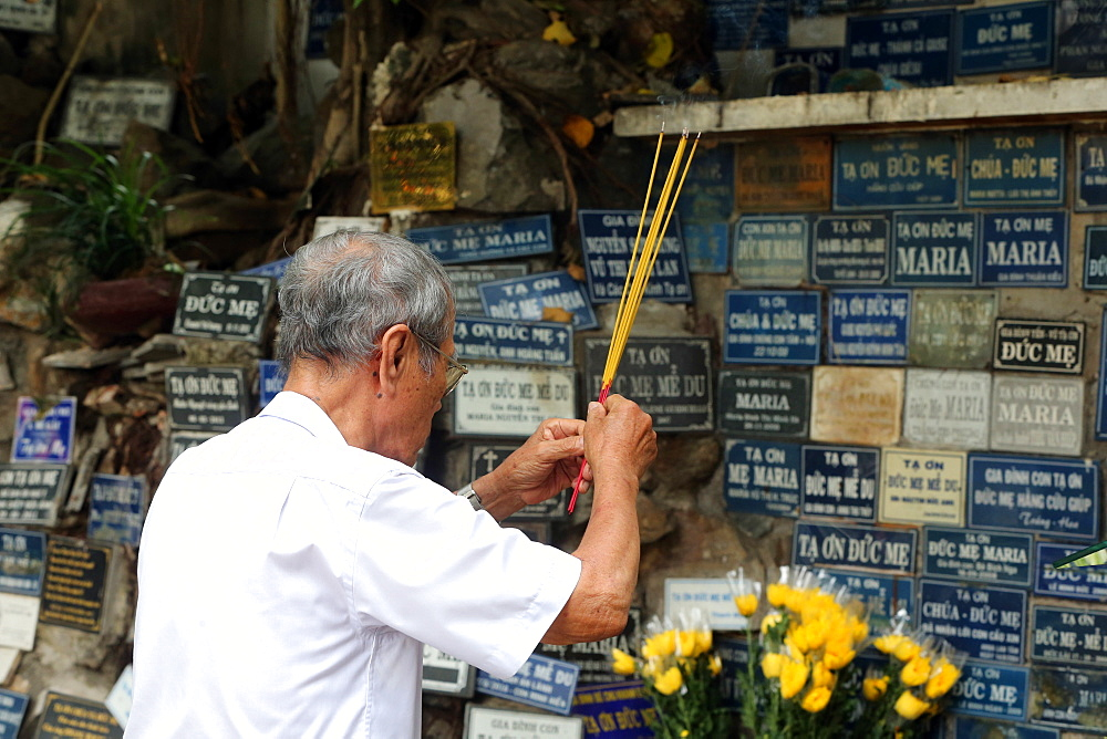 Man praying in copy of the Grotto of Massabielle, St. Philip Church (Huyen Sy Church), Ho Chi Minh City, Vietnam, Indochina, Southeast Asia, Asia