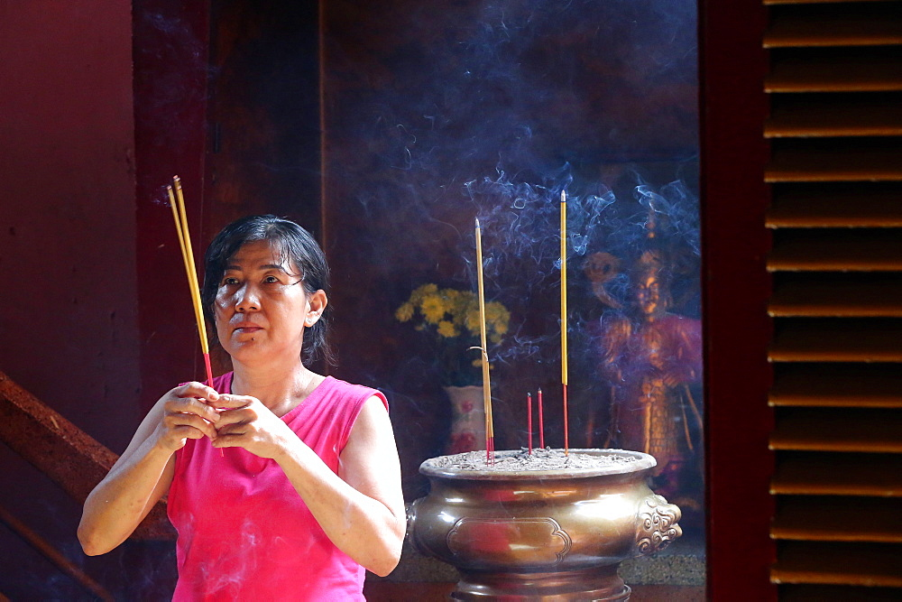 Buddhist worshipper with incense sticks, Khanh Van Nam Vien Taoist pagoda, Ho Chi Minh City, Vietnam, Indochina, Southeast Asia, Asia
