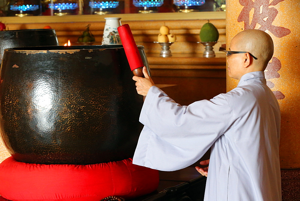 Vietnamese Buddhist nun using a giant singing bowl, Vung Tau, Vietnam, Indochina, Southeast Asia, Asia