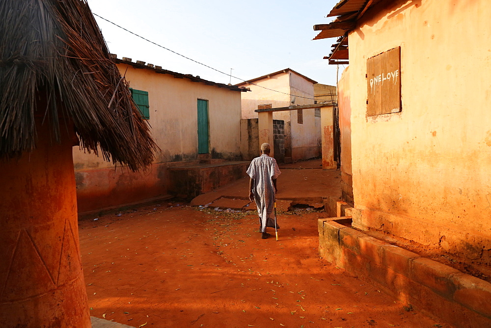 Old man walking in Togoville at sunset, Togoville, Togo, West Africa, Africa