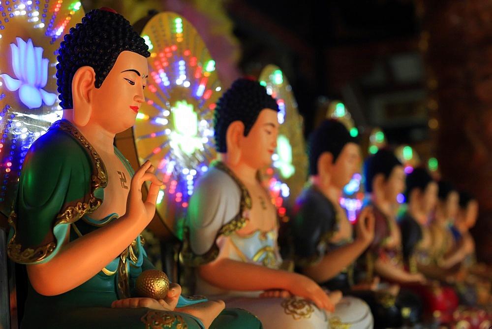 Chua Vinh Nghiem buddhist pagoda. Altar with Buddha statues. The Vitarka mudra.
