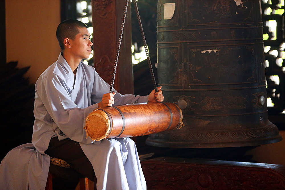 Linh An buddhist pagoda. Young monk ringing bell in monastery. Dalat. Vietnam.