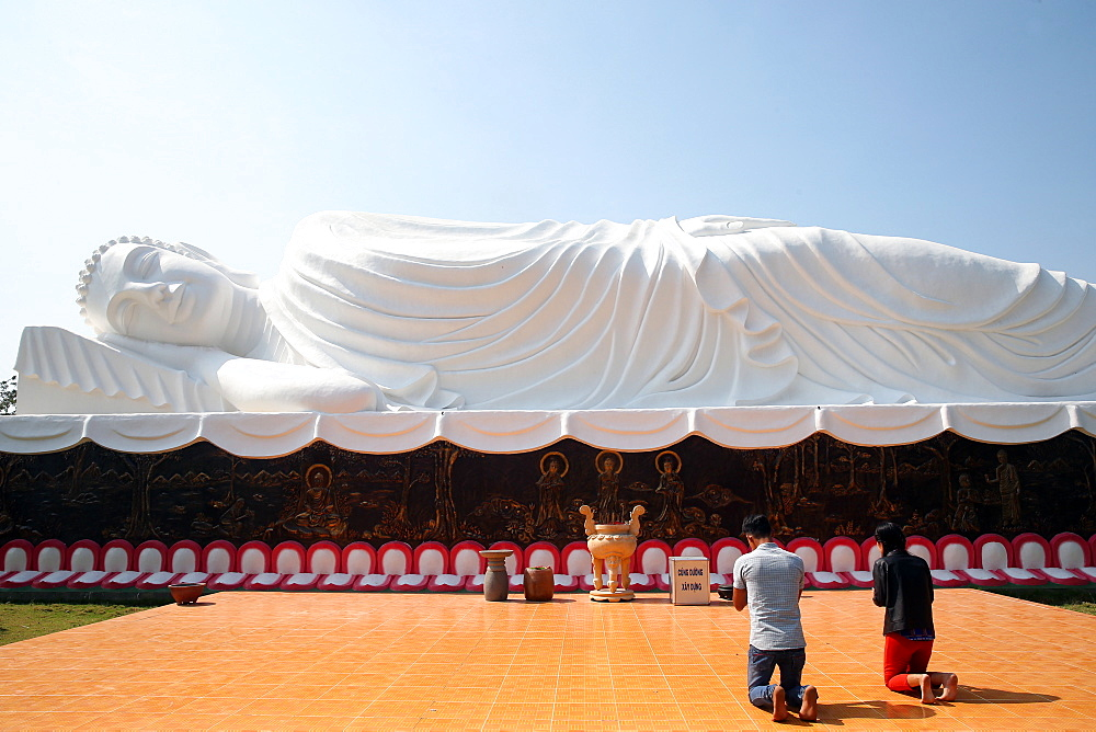 Worshippers praying to the Reclining Buddha, Chua Thien Lam pagoda, Tay Ninh, Vietnam, Indochina, Southeast Asia, Asia