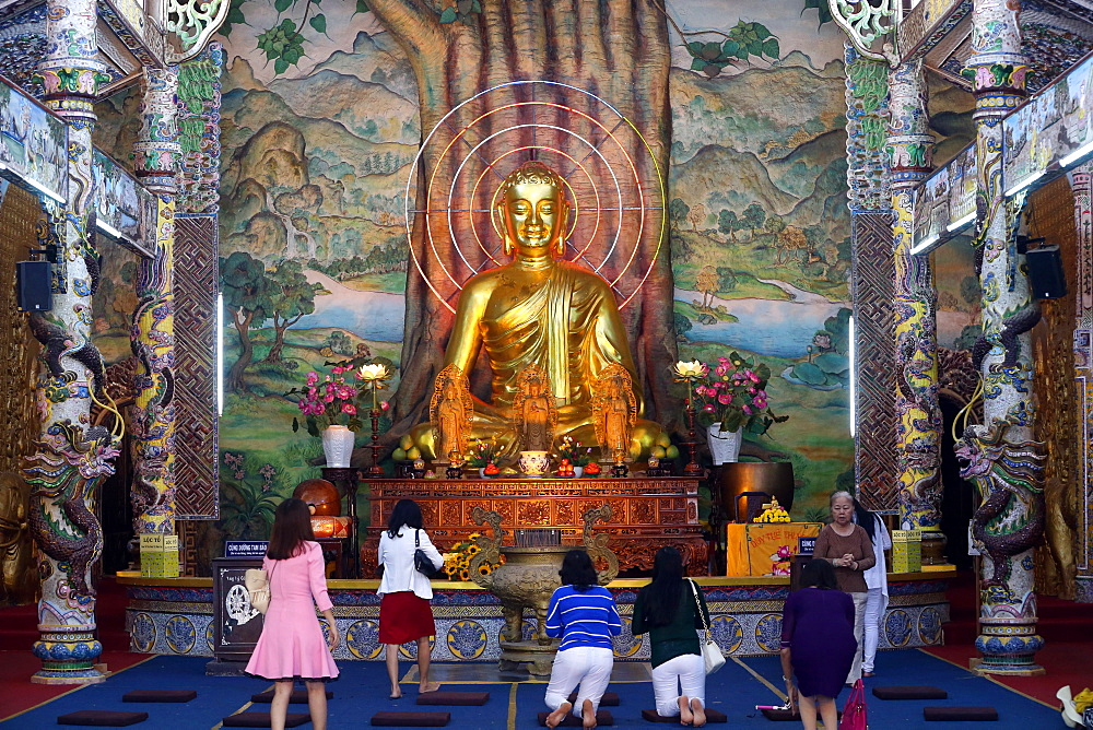 Sitting golden Buddha figure in main hall and worshippers praying to the Buddha, Linh Phuoc Pagoda, Dalat, Vietnam, Indochina, Southeast Asia, Asia