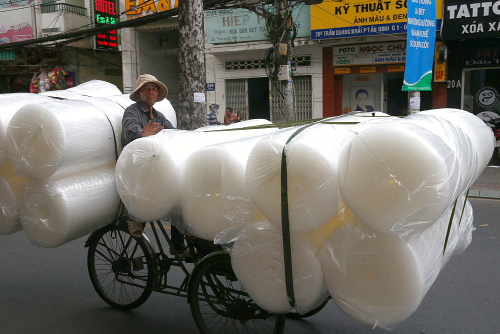Man pedals a trishaw, loaded with rolls on a road. Ho Chi Minh City. Vietnam.