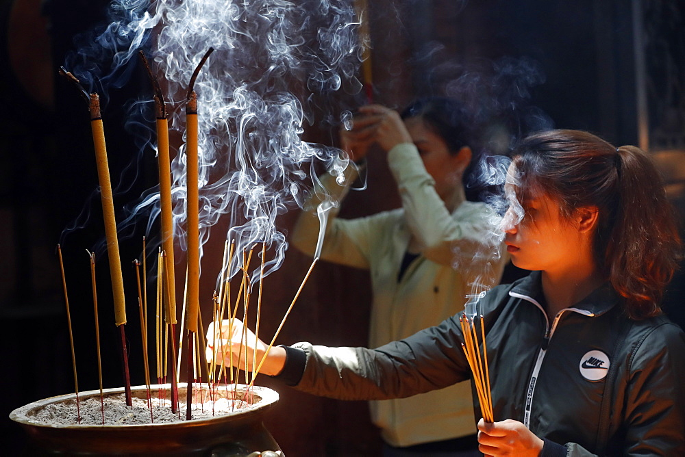 Taoist temple, Emperor Jade pagoda (Chua Phuoc Hai), Buddhist worshipper burning incense sticks, Ho Chi Minh city, Vietnam, Indochina, Southeast Asia, Asia