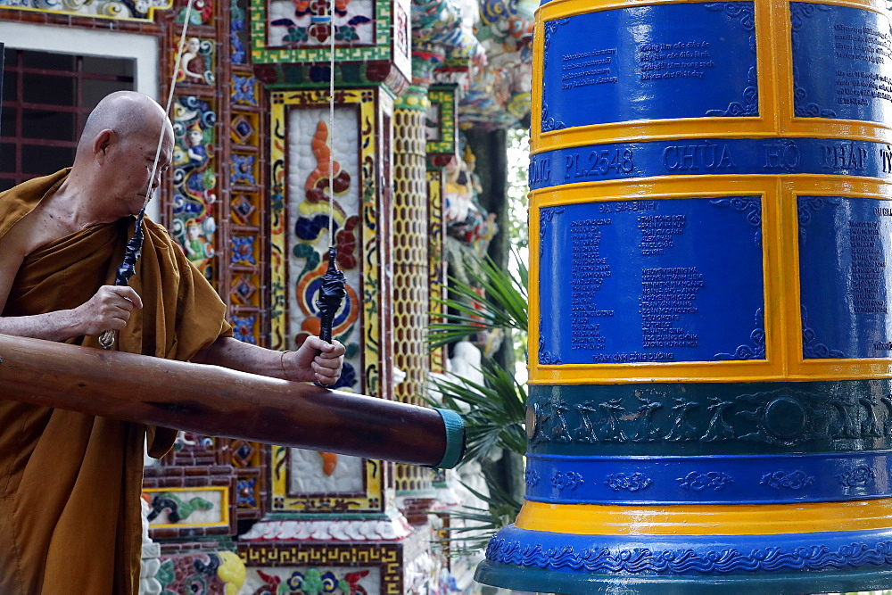 Ho Phap buddhist temple. Young monk ringing bell in monastery. Vung Tau. Vietnam.