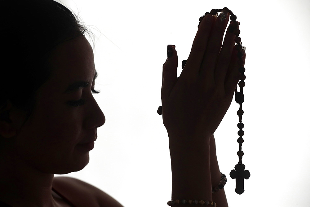 Christian woman praying the Rosary. Vietnam.