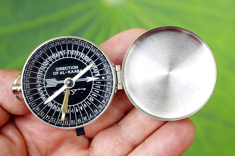 Muslim using a Qibla compass to indicate the direction of Al Kaaba. Close-Up on hand.