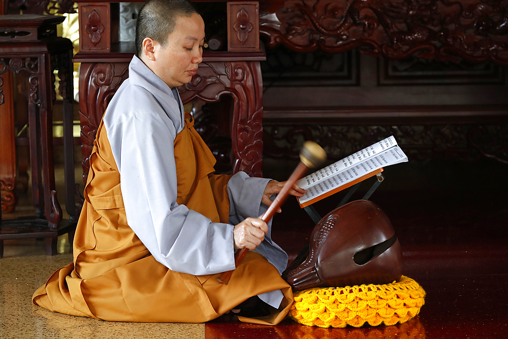 Buddhist ceremony at temple. Monk playing on a wooden fish (percussion instrument). Ho Chi Minh city. Vietnam.