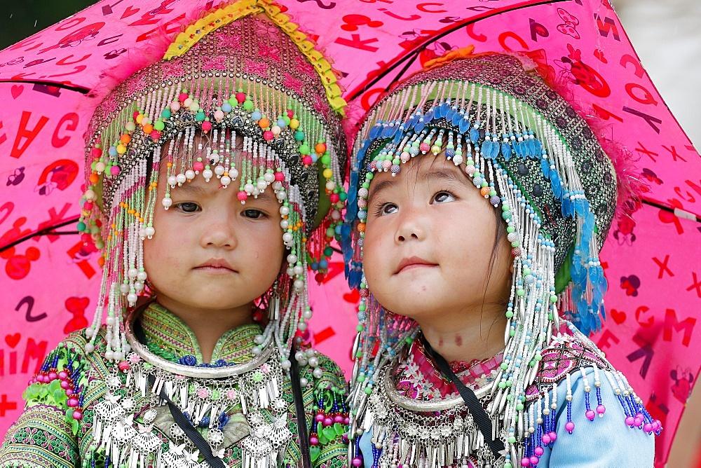 Hmong children under umbrella in the monsoon (rainy) season, Sapa, Vietnam, Indochina, Southeast Asia, Asia
