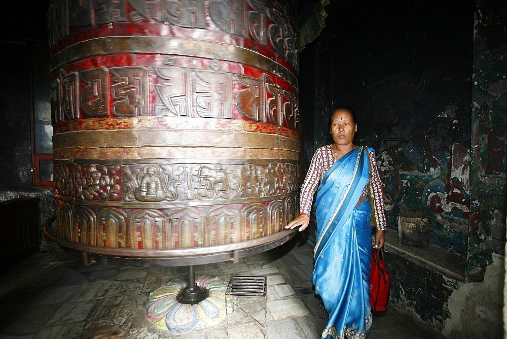 Woman and prayer wheel, Swayambhunath Temple, Kathmandu, Nepal, Asia