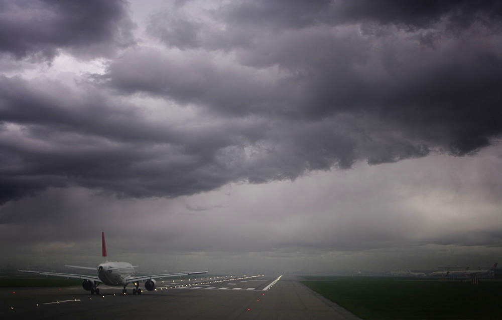 Plane ready for take off and stormy skies, Heathrow Airport, London, England, United Kingdom, Europe - 812-131