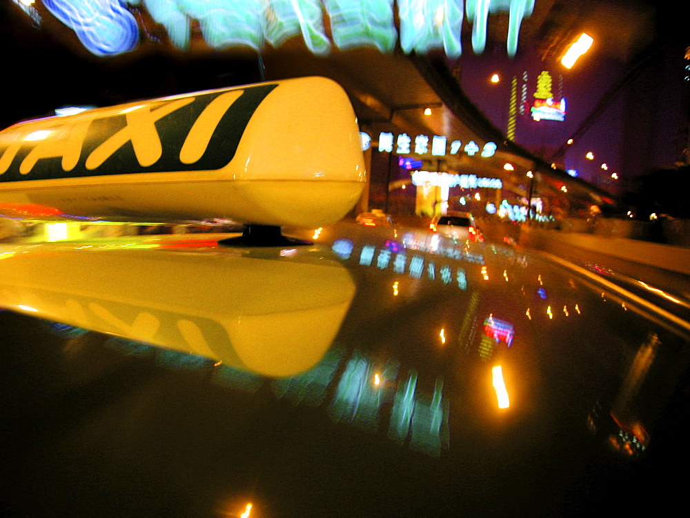 Close up of Taxi sign on car roof with neon road signs, Shanghai, China, Asia