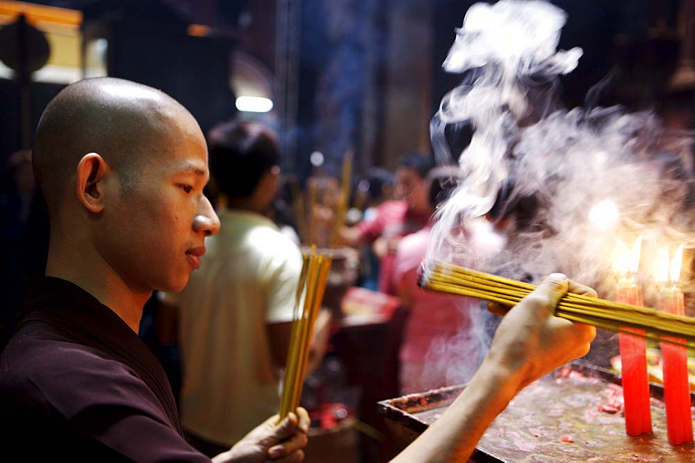 Monk lighting joss sticks during ceremony in a Buddhist temple, Ho Chi Min City, Vietnam, Indochina, Southeast Asia, Asia