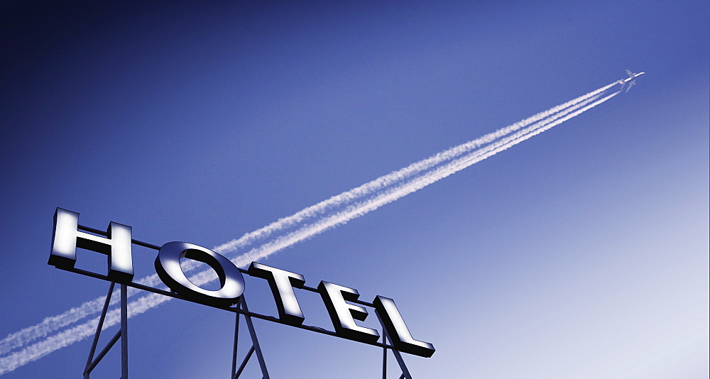 Plane in blue sky with vapour trail and hotel sign - 812-76