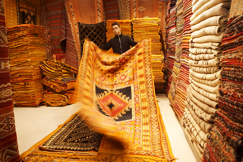 Carpet shop interior with shop keeper showing rug, Marrakesh, Morocco, North Africa, Africa - 812-80