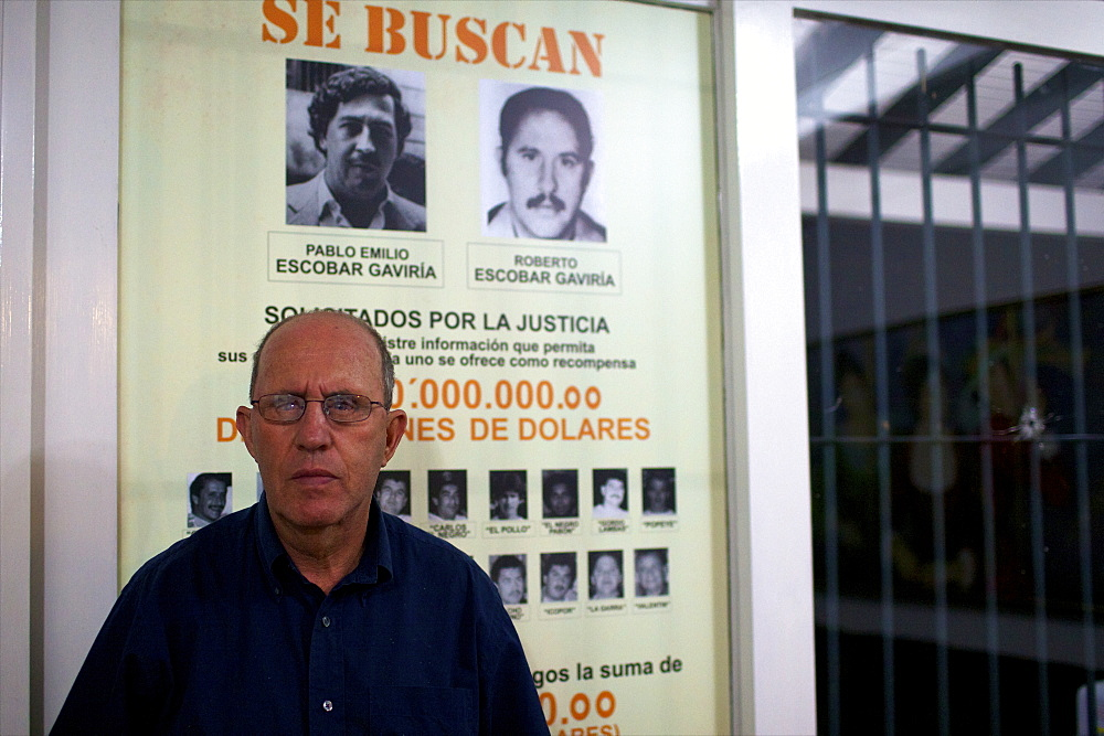 Roberto Escobar in his home of Medellin, under the panel offering 2 millions American dollars for his own capture, Colombia, South America