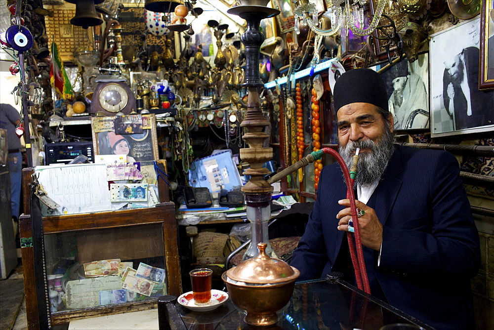 An old man smoking narguile in the bazaar of Isfahan, Iran, Middle East - 814-1508