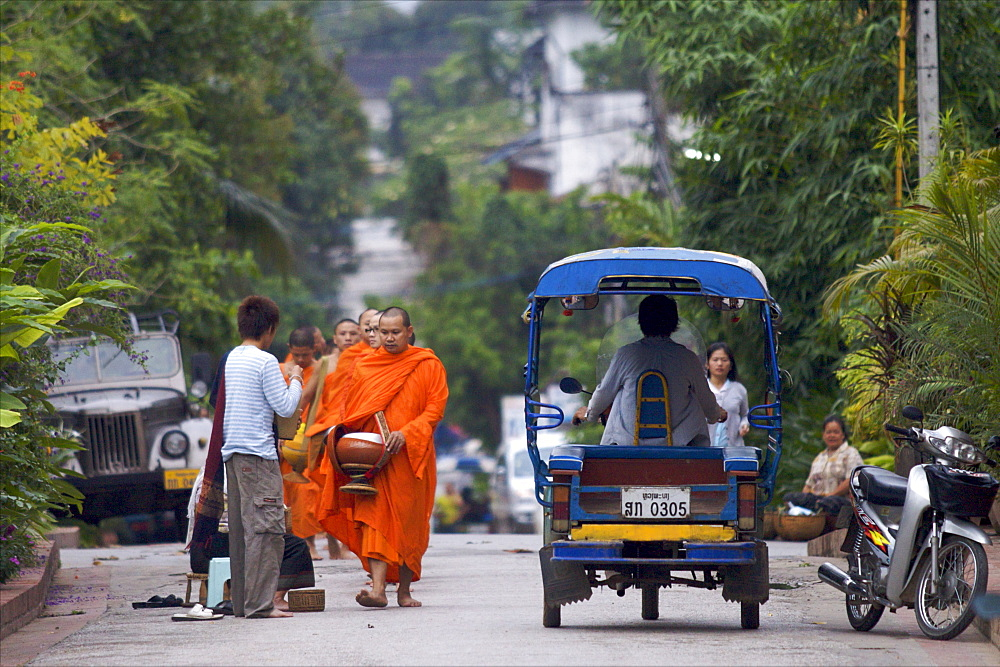 Monks during the dawn procession for food in the streets in Luang Prabang, Laos, Indochina, Southeast Asia, Asia