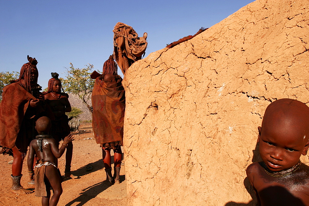A Himba family in a village on the Kunene River, close to Epupa falls, on the border with Angola, Namibia, Africa