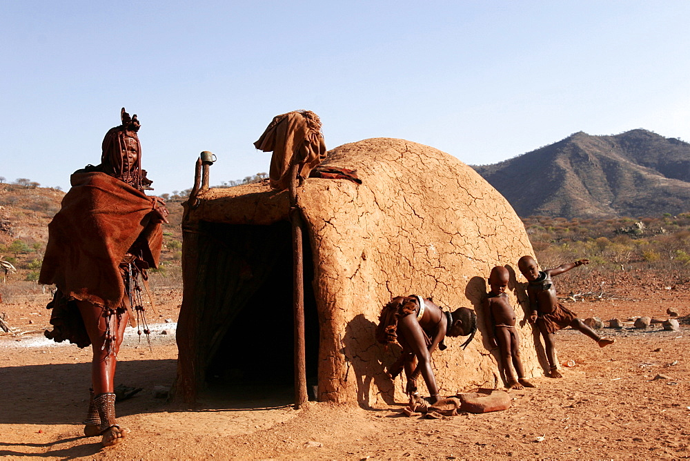 A Himba woman and children outside her house in a village on the Kunene River, on the border with Angola, Namibia, Africa