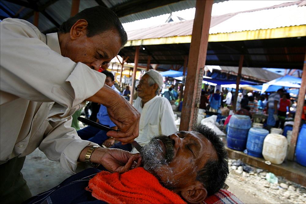Barber at the market of Parapat, close to Lake Toba, Sumatra, Indonesia, Southeast Asia, Asia