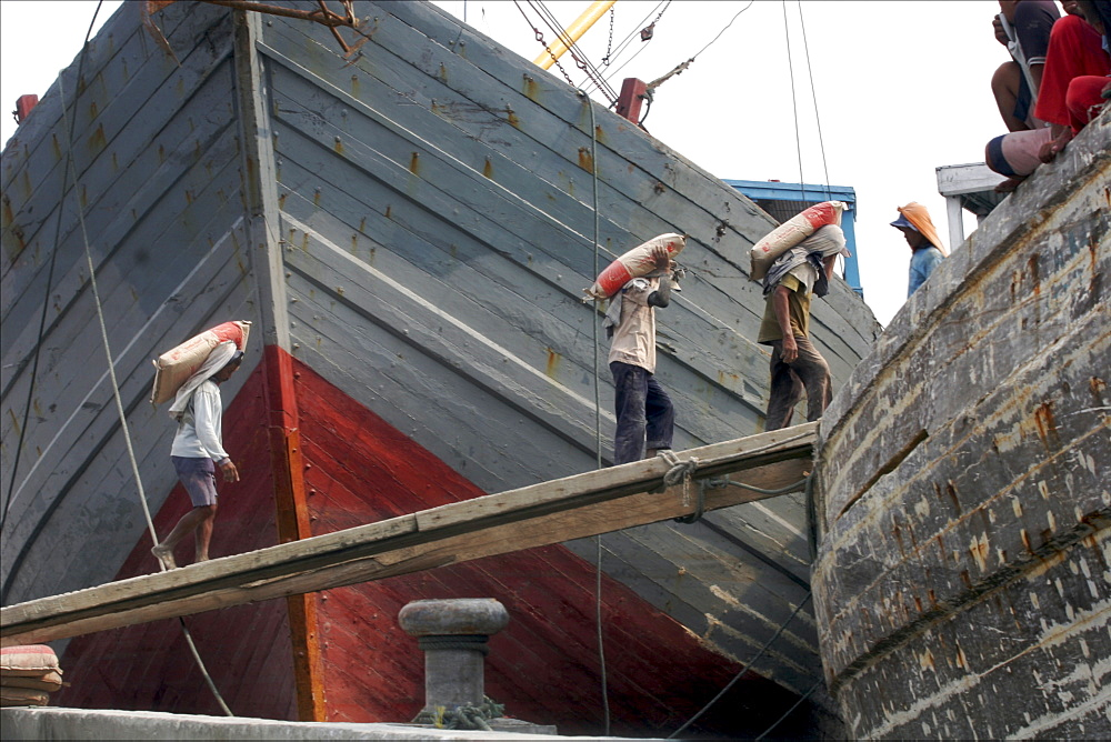 Coolies carrying bags of cement onto schooner, Sunda Kelapa, harbour of Jakarta, Java, Indonesia, Southeast Asia, Asia