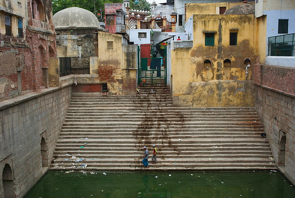 Water spilled on stairs and buildings with two men at the bottom of the stairs, Delhi, India, Asia - 815-2219