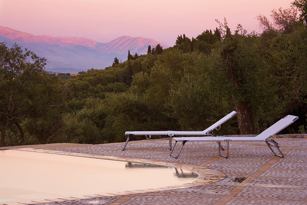Sun loungers on pool terrace at sunset, Kerkyra, Corfu, Ionian Islands, Greek Islands, Greece, Europe