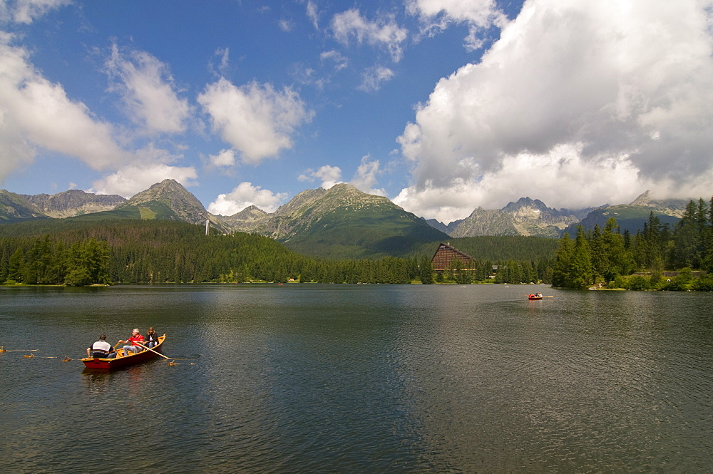 Tourists in a canoe at the Glacier lake of Strebske Pleso in the High Tatra, Slovakia, Europe