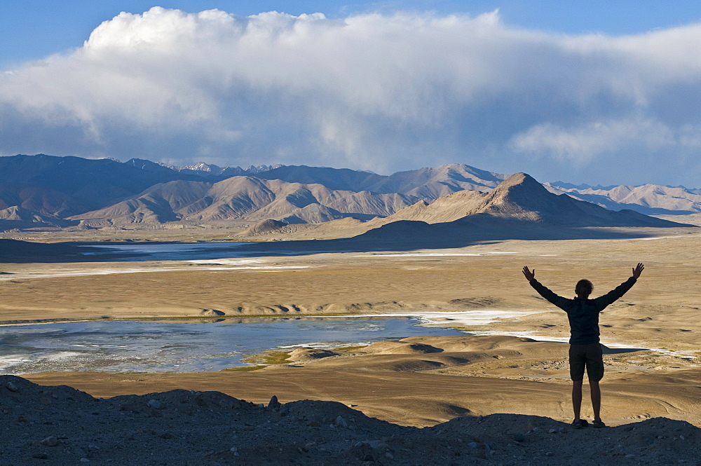 Tourist admiring the stunning scenery of Tuz Kul, Pamir, Tajikistan, Central Asia