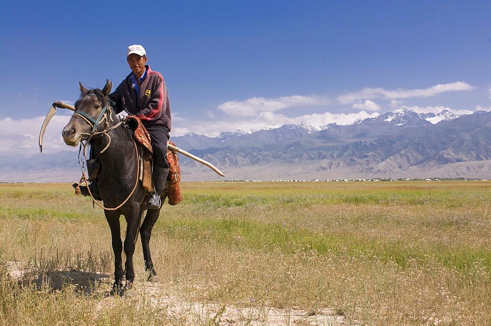Kyrgyz man on his way to harvest, Torugat Pass, Kyrgyzstan, Central Asia, Asia