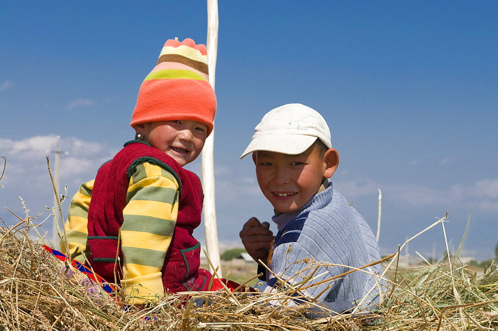 Two young kids on a carrier loaded with hay, Torugat Pass, Kyrgyzstan, Central Asia, Asia