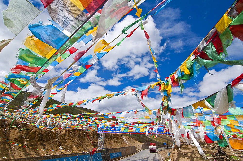 Prayer flags crossing the Friendship Highway between Lhasa and Kathmandu, Tibet, China, Asia