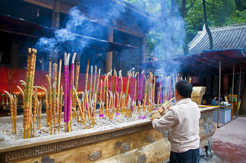 Burning sticks of Tibetan incense in a monastery above the giant Buddha of Leshan, Sichuan, China, Asia