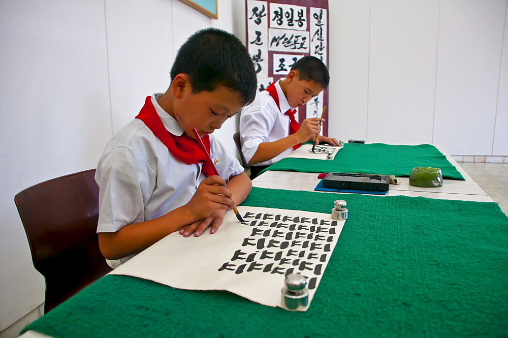Young boys practising calligraphy in the Schoolchildrens palace, Pyongyang, North Korea, Asia
