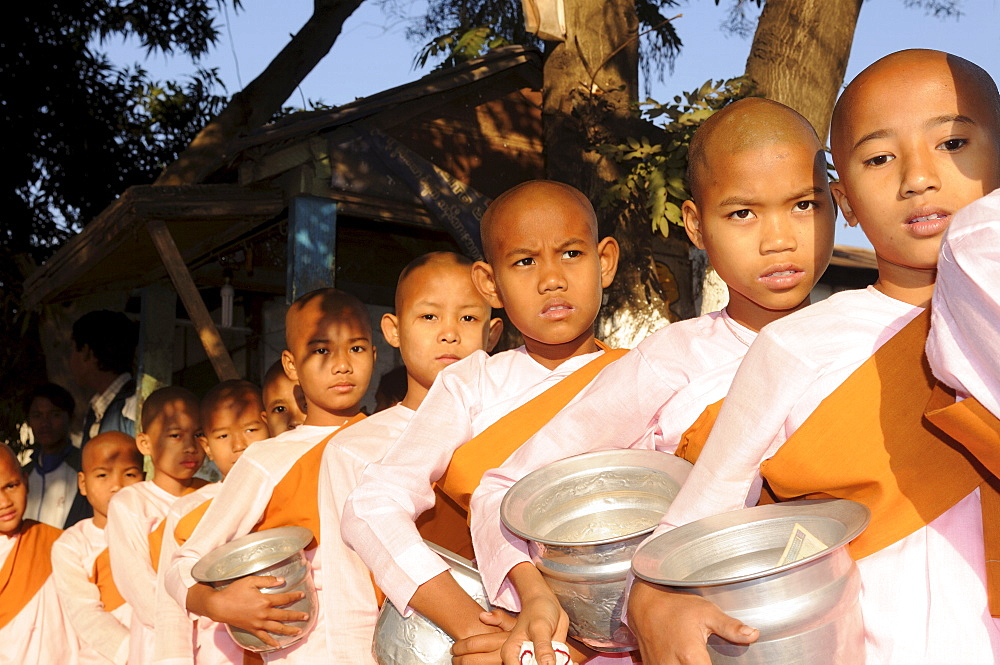 Young female monks waiting to receive rice from donors, Pyay, Myanmar, Asia