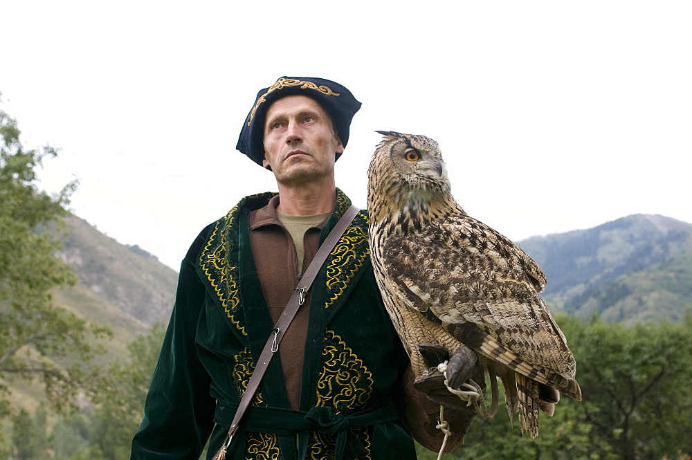 Kyrgyz eagle hunter with a rock eagle-owl (Bubo bengalensis), Sunkar Eagle Farm, Kazakhstan, Central Asia