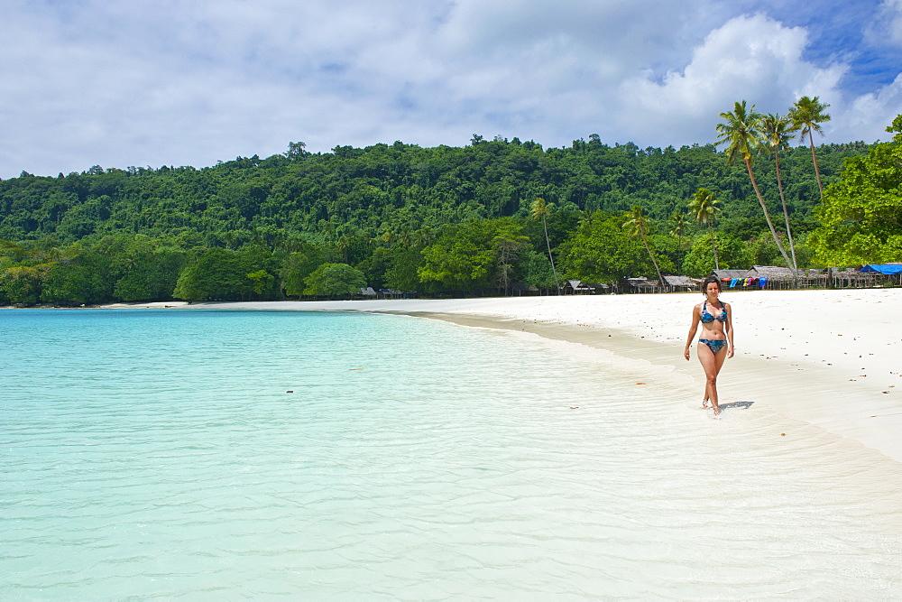 Tourist wandering along the turquoise water and white sand at the Champagne beach, Island Espiritu Santo, Vanuatu, South Pacific, Pacific