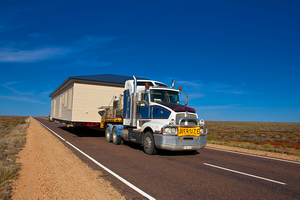 Truck transporting a full house on its trailer in the Outback of South Australia, Australia, Pacific