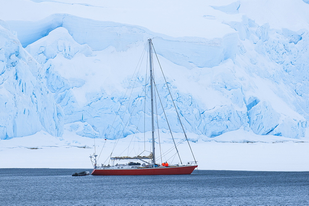 Sailing boat below a huge icefield near Port Lockroy research station, Antarctica, Polar Regions