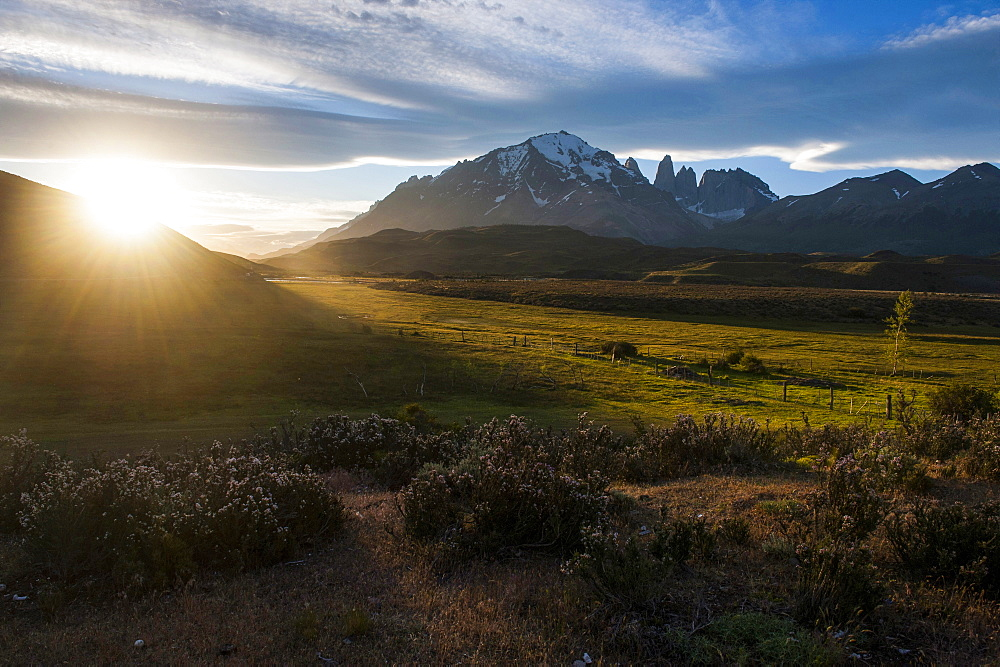 Late sunrays breaking through the clouds before the towers of the Torres del Paine National Park, Patagonia, Chile, South America