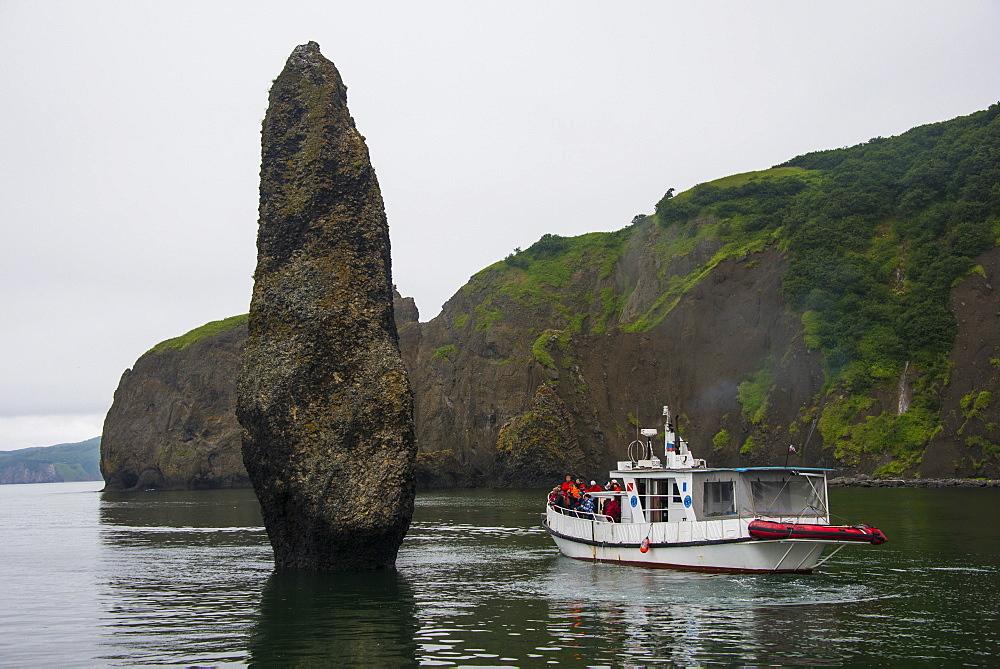Little tourist boat ships beside a large monolith in the Avacha Bay near Petropavlovsk-Kamchatsky, Kamchatka, Russia, Eurasia