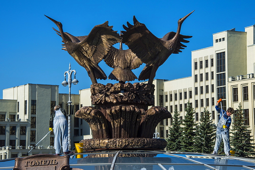 Woman cleaning a giant bird statue on top of a glass cupola on Nezalezhnasti Independence square, Minsk,Belarus, Europe