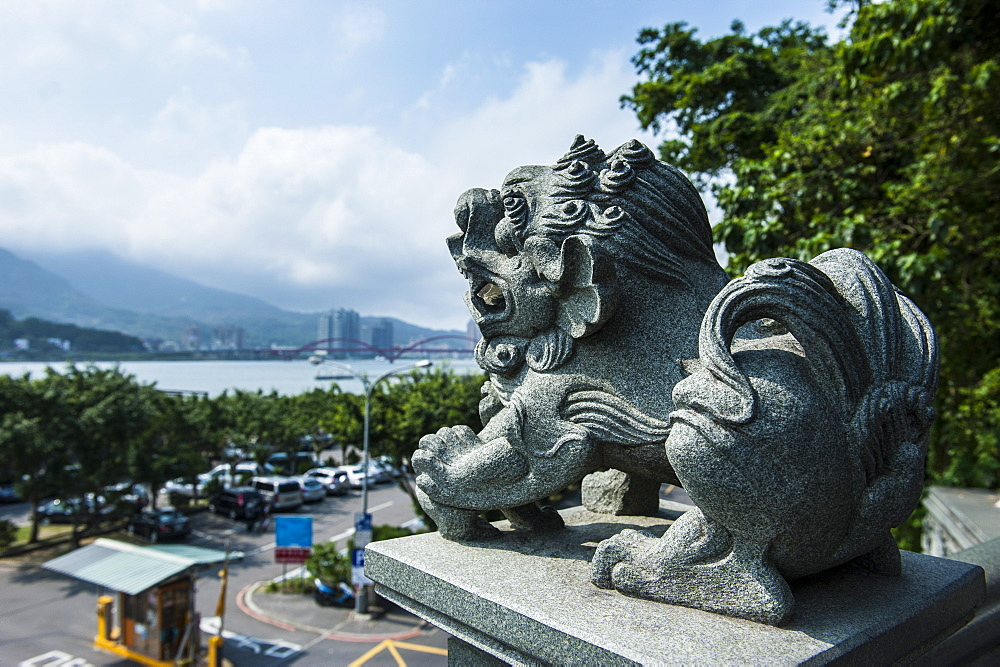 Stone lion overseeing the Danshui river from the Guandu Temple, Guandu, Taipei, Taiwan, Asia