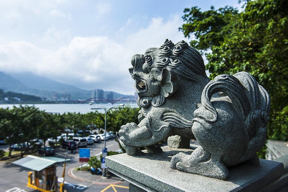 Stone lion overseeing the Danshui river from the Guandu Temple, Guandu, Taipei, Taiwan, Asia